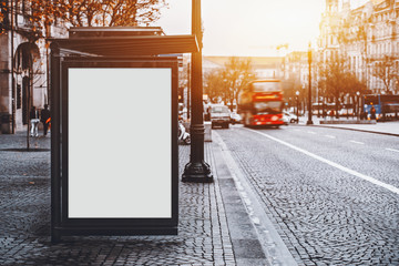 White empty information mock-up on city bus stop, blank vertical billboard near paved road with red touristic bus, clear placeholder frame in urban settings with copy space for text or advertising