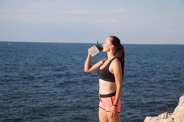 Fitness girl drinks water sport training