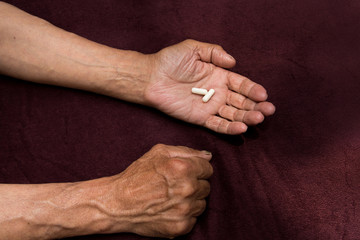 Two white pills in old men's hands . Painful old age. Health care of older people.