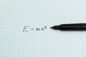 E=MC2 in a school notebook in a cage.