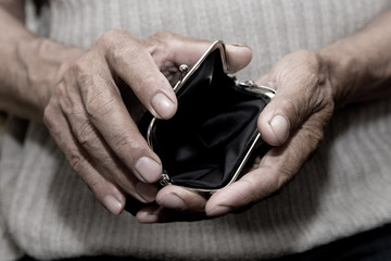An elderly man holds an empty purse. The concept of poverty in retirement . Wall mural