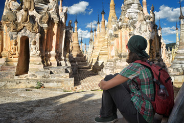 Hiker with backpack sit and look Buddhist stupas in Burma