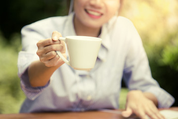 Woman give coffee cup with happy emotion, vintage color tone.