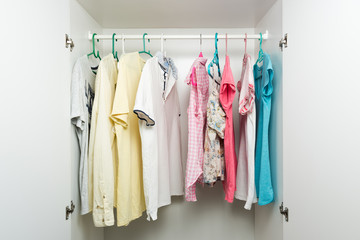 Clothes hanging on rail in white wardrobe. Men's and women's summer clothes, pastel colors