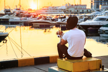 Stylish man and his dog sitting together on pier and enjoying colorful sunset. Jack russell terrier puppy on his lap. Luxury yachts docked in sea port.