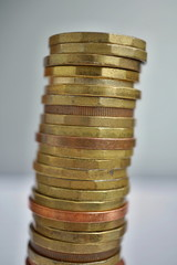 Side view of tall pile of metal coins in golden and copper color in front of silver background