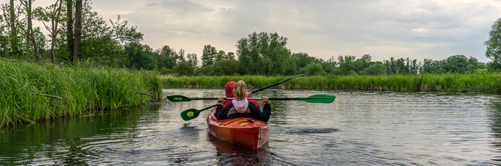 Two girls kayaking panorama