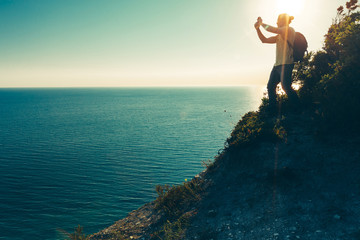 Traveler man stands on the top and takes pictures of sea on cell phone camera during sunset