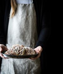 Woman holding tray of cinnamon buns