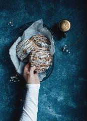 Left hand holding cinnamon bun, blue background