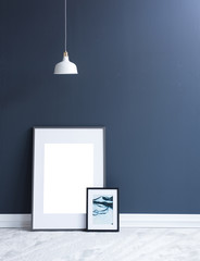 two frames and lamp concept on the dark blue wall