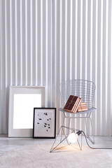 modern metal chair and books with frames and lamp concept in front of the white panel