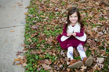 Young girl sat in in autumn leaves outside