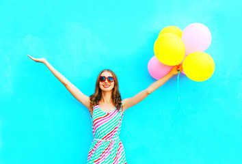 happy smiling woman and an air colorful balloons is having fun on a blue background Wall mural