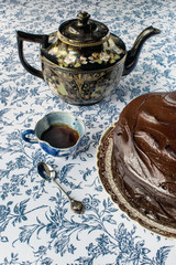 Chocolate icing cake on blue flower background with coffee pot, cup, and spoon