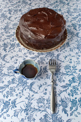 Chocolate icing cake on blue flower background with coffee and fork
