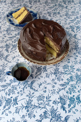 Chocolate icing on yellow cake with slice cut out with coffee on blue flower background