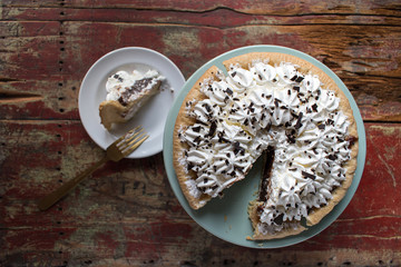 Chocolate pie with cut slice on rustic table