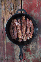 bacon strips in cast iron pan on rustic wooden table in top down view