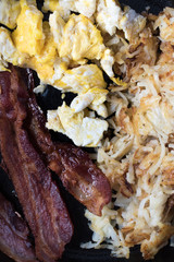 Scrambled eggs, bacon, and hashbrowns closeup in cast iron pan