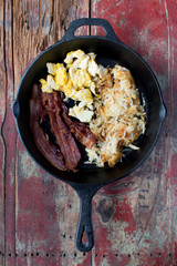 Scrambled eggs, bacon, and hashbrowns in cast iron pan on rustic table