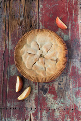 handmade apple pie on rustic table with apple slices