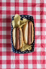 Fourth of July cookout with two hog dogs and chips on checkerboard tablecloth