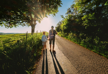 Father and son walk on sunset road