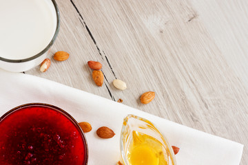 Honey, raspberry jam, milk, towel on rustic background. Candied fruits on a towel. Healthy food. Breakfast. White napkin on the table. The background. Frame