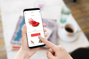 Add to cart red shoes on online store. Modern smart phone with round edges in woman hand. Table with coffee and magazines in background.
