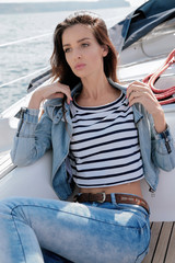 beautiful woman with dark hair relaxing on yacht in open sea