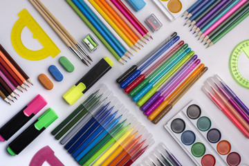 A lot of stationery on the white surface, diagonal rows, top view, background