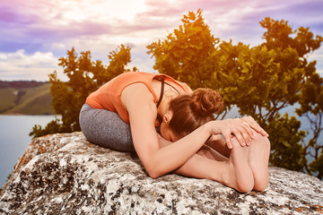 Close-up of young woman doing yoga exercise on the stone against landscape.