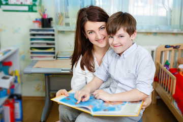 Beautiful happy mother with child boy 10 years old reading book, sitting on chair in children's room at home