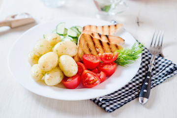 Useful, hearty and delicious breakfast or dinner, boiled potato with dill, cherry tomato, cucumber, white bread toast, vegetable or olive oil and mineral sparkling water on a light wooden background