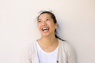 Close up asian woman smiling against by  white wall
