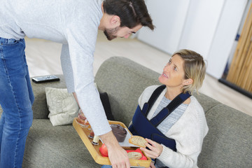 Man serving tray of food to injured lady