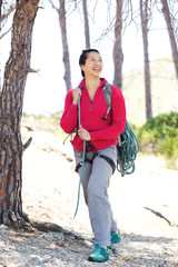 Full length smiling asian female hiking in the forest