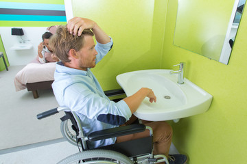 Disabled man styling hair at sink