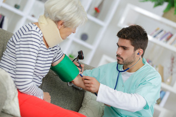 Young male doctor taking elderly woman's blood pressure at home