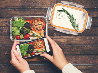 Female hands taking photo of salad and chiken lunch box with smart phone. Close up of woman hands taking picture of food.