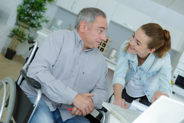 Young lady talking to man in wheelchair