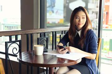 Young business woman with smartphone and coffee