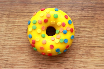 Single yellow donut on a wood background