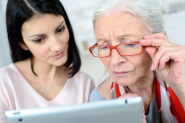 Lady helping elderly woman use computer