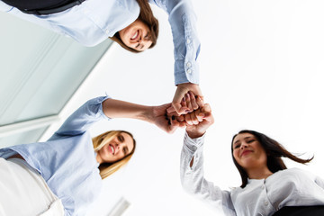 Three successful women celebrate their success by getting their hands together