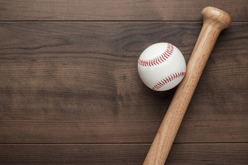 closeup of baseball bat and ball on wooden table with copy space