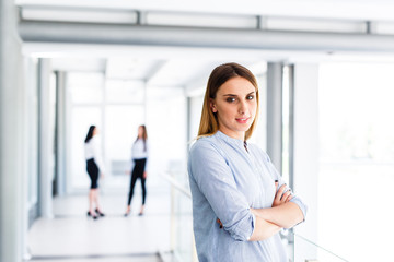 Blonde business woman standing and crossed her arms while there are her work colleague behind