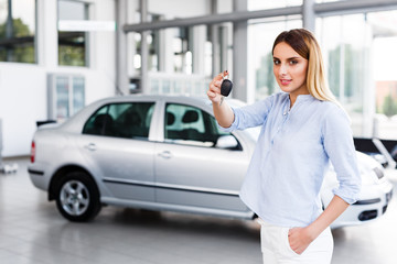 Blonde business woman standing in modern car dealership and holding car key