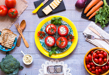 Stuffed tomatoes with cheese, and different vegetables, on a wooden background,